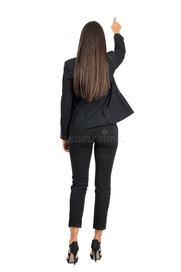 Вид сзади бизнес-леди в элегантном костюме указывая что-то перед ей стоковое изображение
