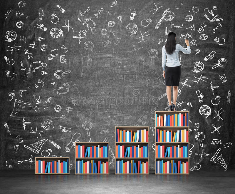 Вид сзади женщины которая рисует воспитательные значки на огромной доске мела Лестница сделанная из книжных полок стоковое фото