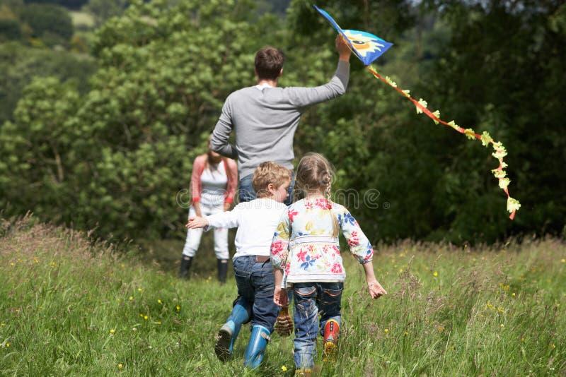 Вид сзади змея летания семьи в сельской местности стоковые фото
