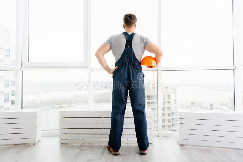 Вид сзади инженера по строительству и монтажу стоя около большого окна стоковые фотографии rf