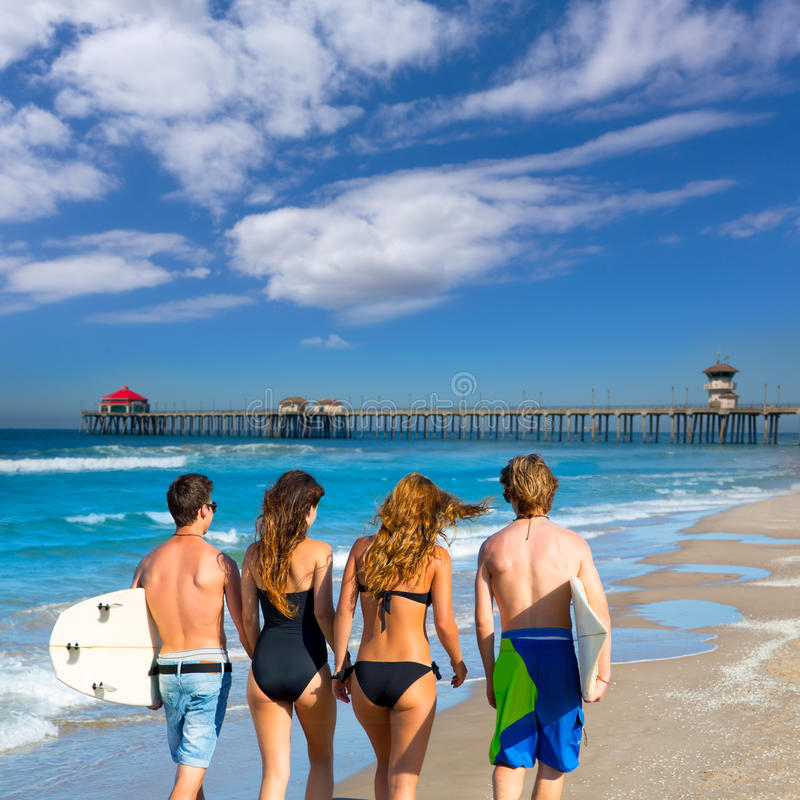 Вид сзади мальчиков и девушек серферов идя на пляже стоковые фотографии rf
