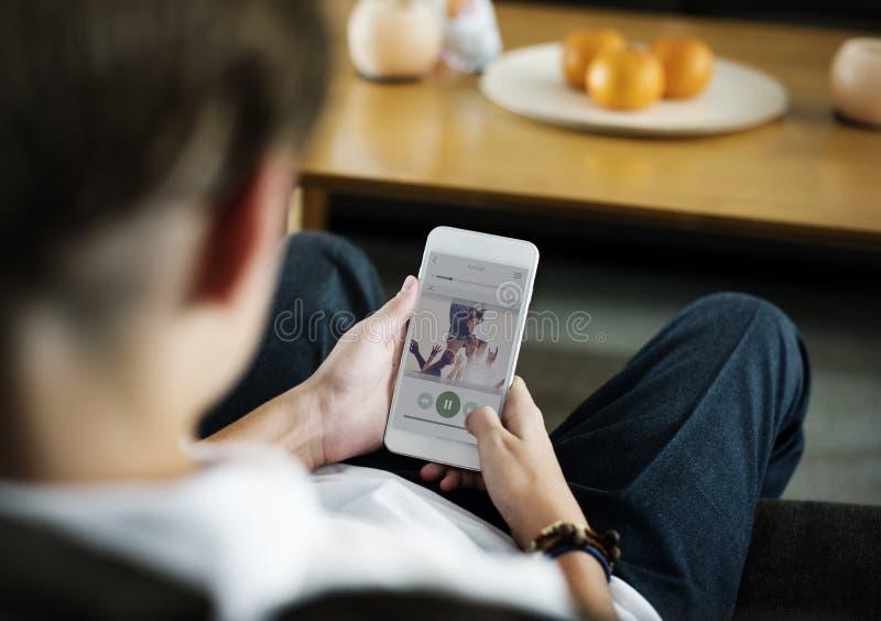 Вид сзади молодого кавказского мальчика используя мобильный телефон стоковые фотографии rf