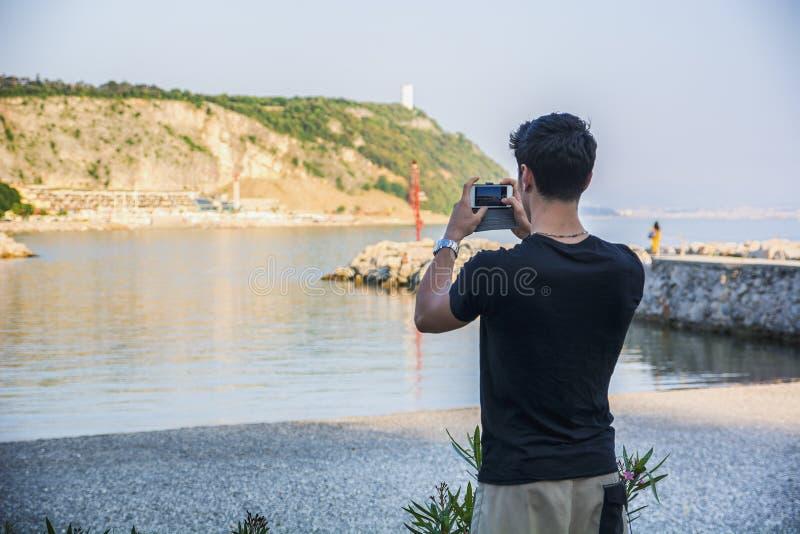 Вид сзади молодого человека принимая фото на пляж стоковая фотография rf