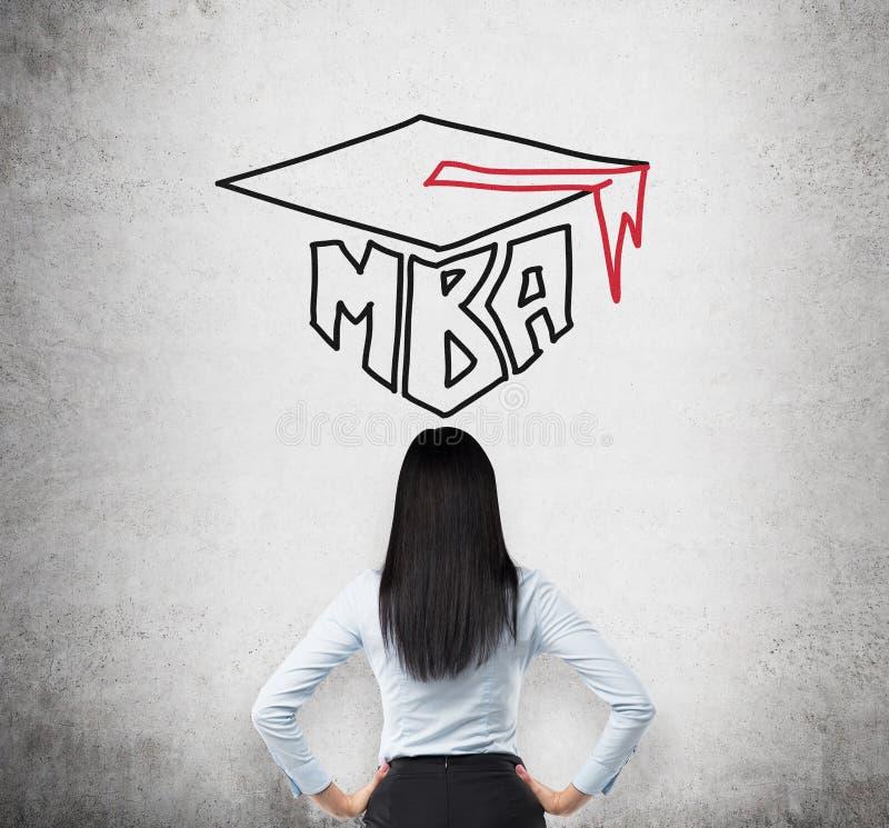 Вид сзади молодой дамы брюнет которая думает о степени MBA стоковое изображение rf