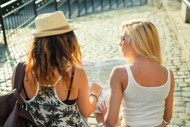 Вид сзади 2 молодых женщин с картой города в поисках привлекательностей Молодые туристские подруги путешествуя на праздниках стоковые фотографии rf