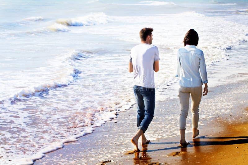 Вид сзади пар идя на пляж стоковые фотографии rf