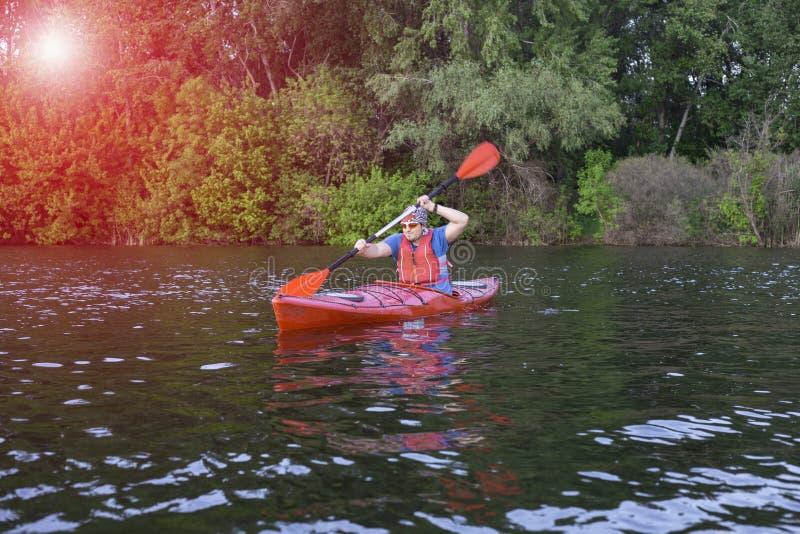 Вид сзади человека полоща каяк в озере с женщиной в предпосылке Соедините сплавляться в озере на солнечный день стоковое фото rf