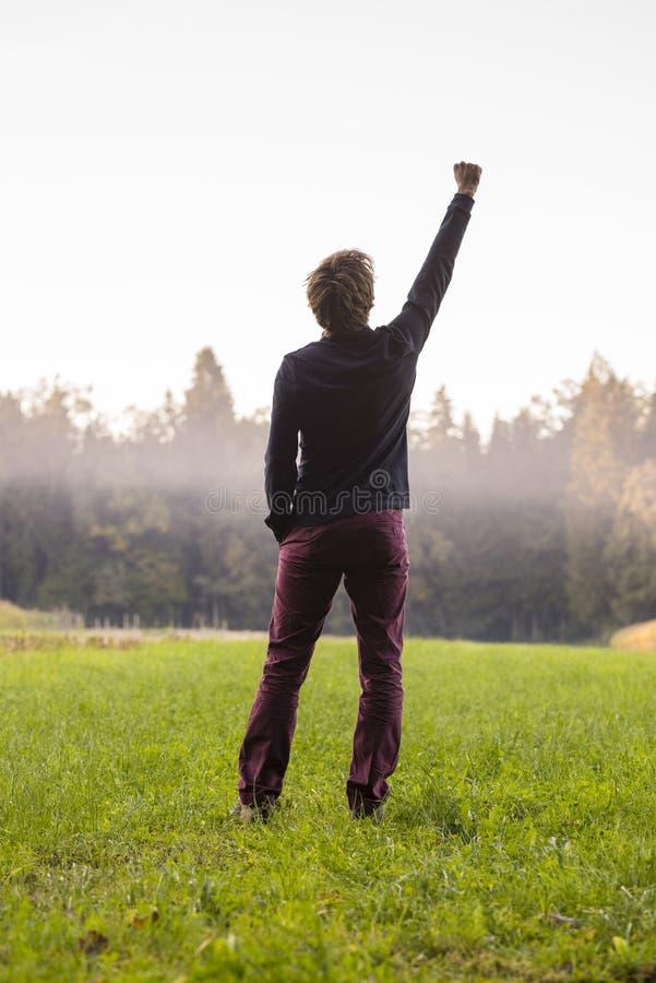Вид сзади человека стоя в зеленом луге при одна поднятая рука стоковая фотография rf