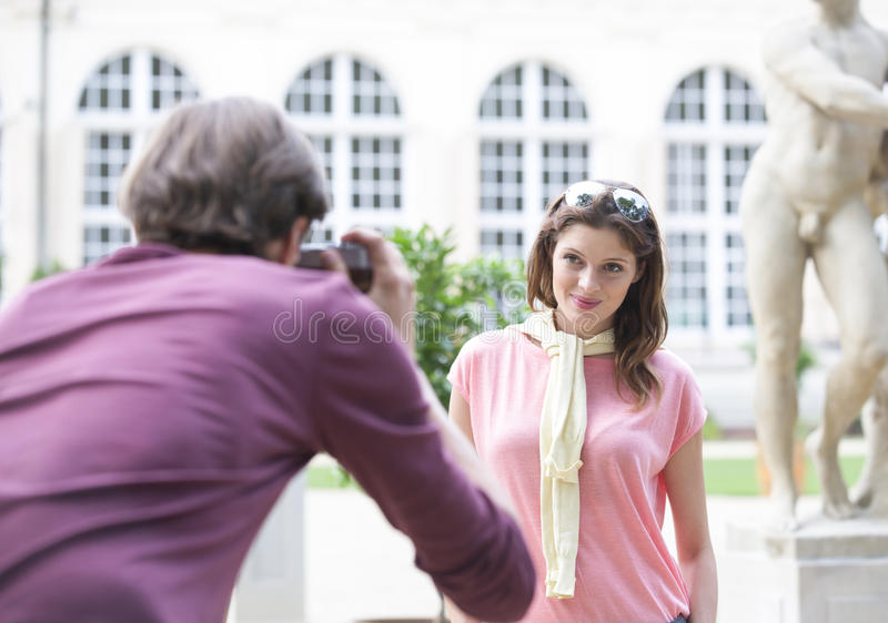 Вид сзади человека фотографируя женщину против здания стоковое изображение