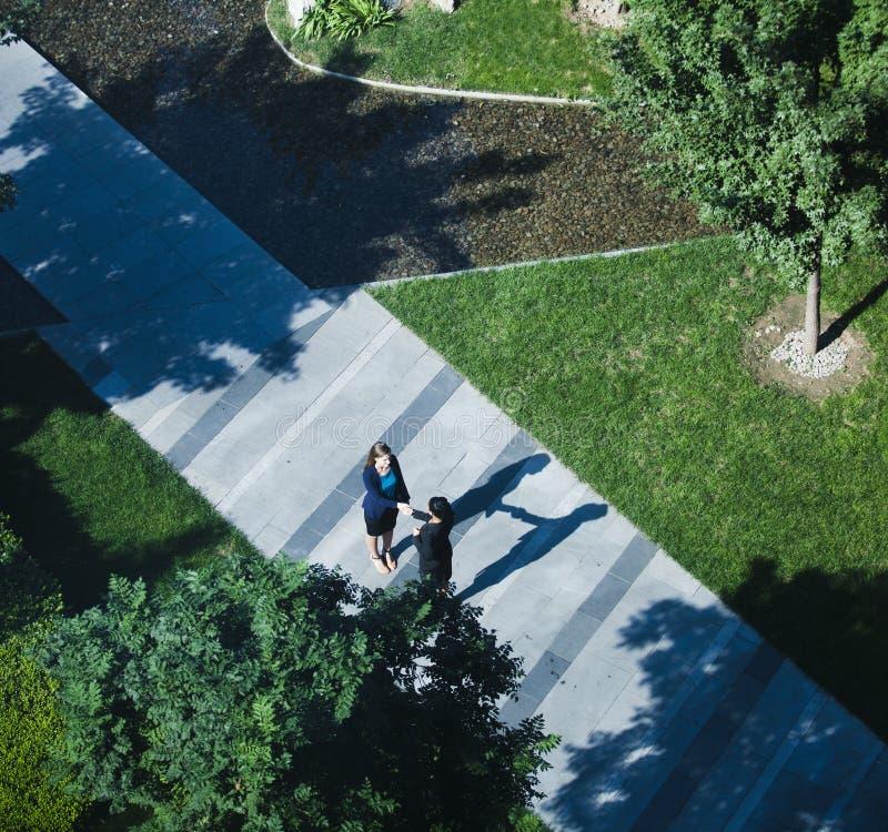 Вид с воздуха 2 коммерсанток тряся руки на тротуаре стоковое фото rf