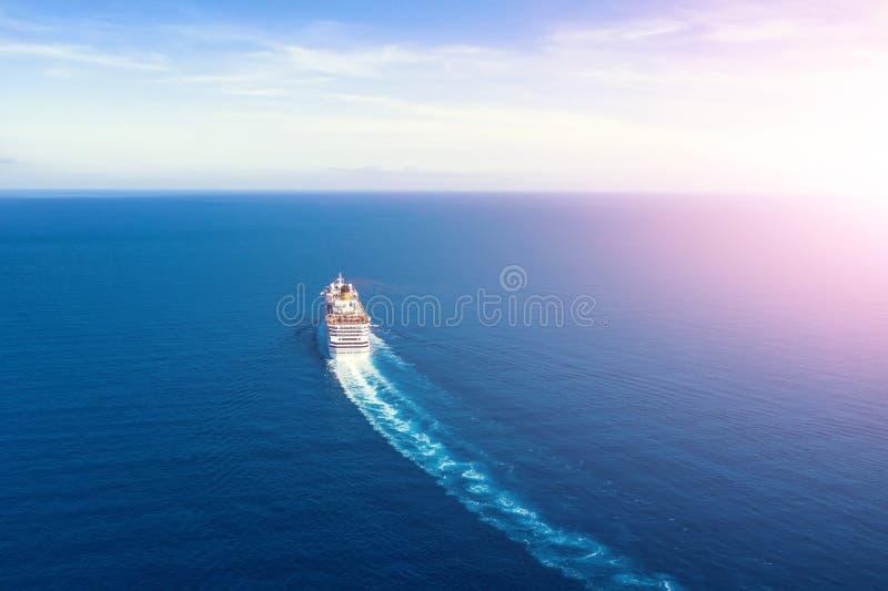 Вкладыш туристического судна идет в горизонт голубое море выходя шлейф на поверхность seascape воды во время восхода солнца r стоковое изображение