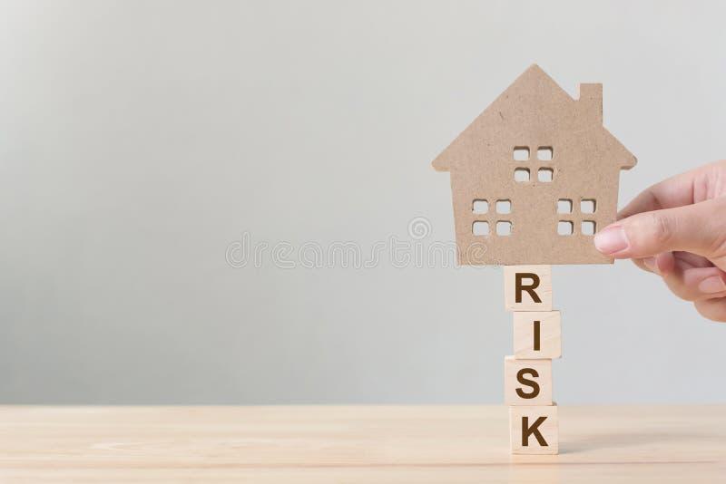 Вклад свойства и ипотека дома финансовая Концепция управления при допущениеи риска Рука кладя деревянный дом стоковые изображения rf