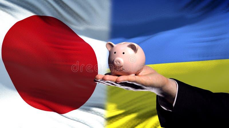 Вклад Японии в Украине, руке бизнесмена держа piggybank, предпосылку флага стоковое фото