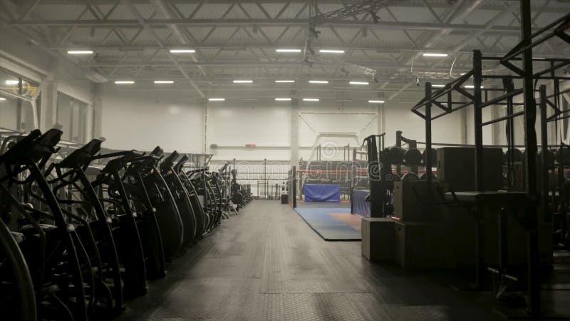 Включать свет на пустом спортзале фитнеса E Темная предпосылка спортзала с велотренажерами и оборудованием фитнеса стоковое изображение