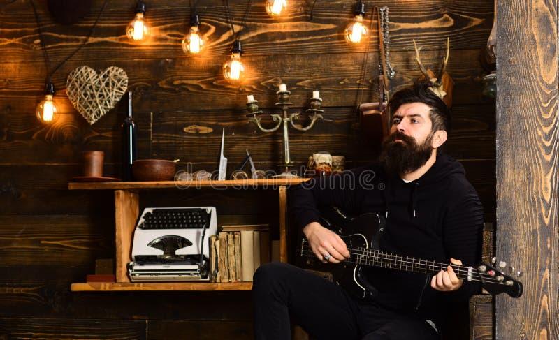 Включенный в релаксацию Музыкант человека бородатый наслаждается выровняться с басовой гитарой, деревянной предпосылкой Человек с стоковая фотография