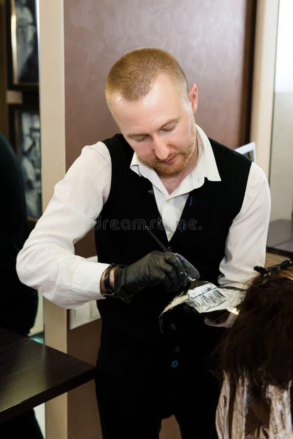 Включенный парикмахер умирая волосы девушки с щеткой стоковое изображение rf