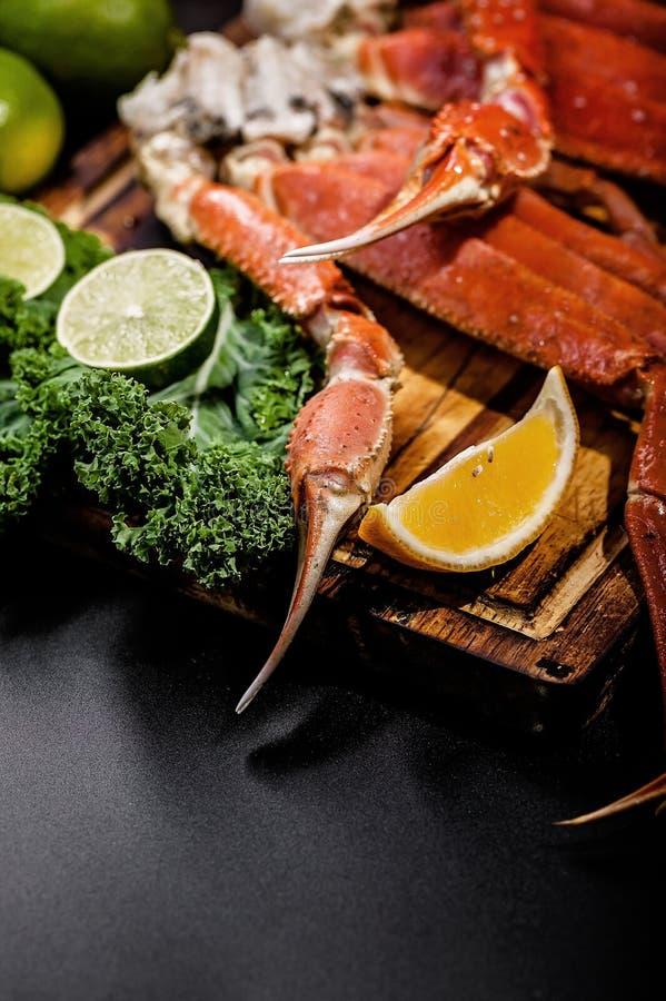 Вкусная морская деликатность Крабовые когти с зелеными, липами и апельсинами на деревянном столе Вертикальный выстрел Закрыть стоковое изображение rf