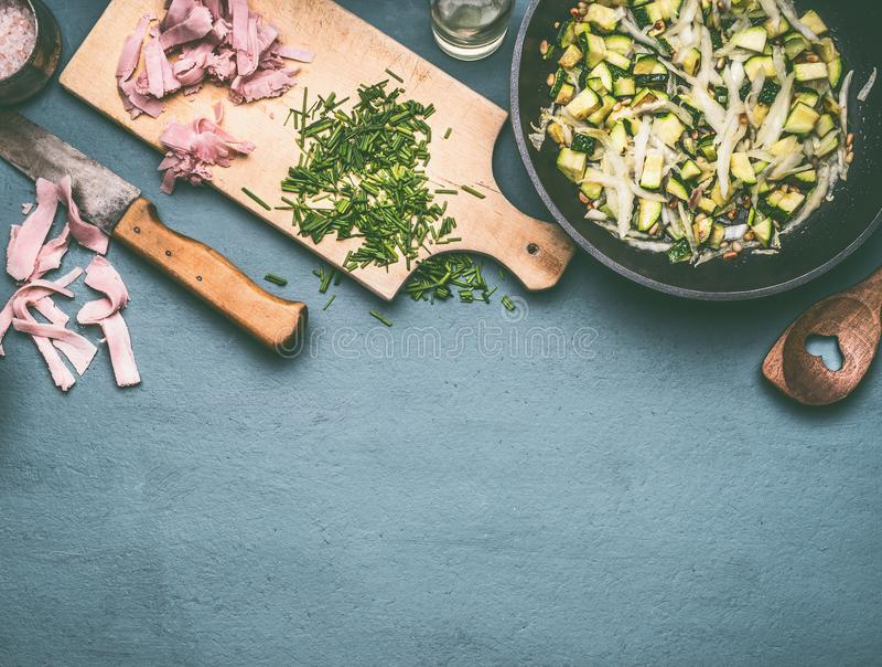 Вкусное блюдо цукини и ветчины в варить лоток на кухонном столе с ингридиентами стоковое изображение rf