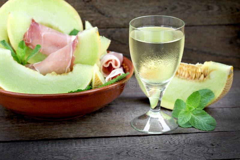 Вкусное, качественное вино и канталупа дыни с закуской ветчины - здоровой и очень вкусной, едой стоковое фото