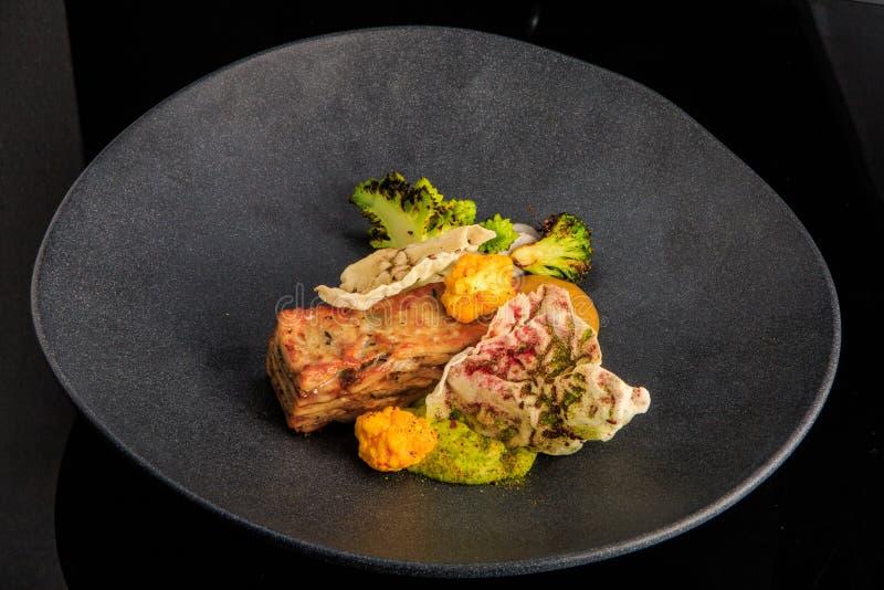вкусное мясное блюдо ресторана с соусом и овощами стоковые фото