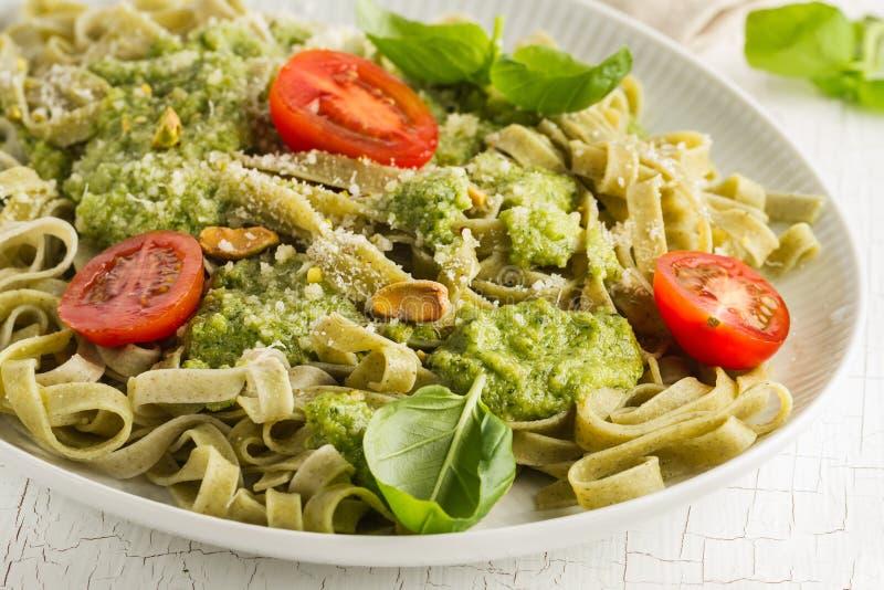 Вкусные аппетитные итальянские макаронные изделия с pesto, томатами и pi соуса стоковое изображение rf