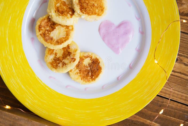 Вкусные блинчики на желтой стойке плиты на деревянное доск-дневном в любов, завтрак сыра в кровати стоковые фотографии rf
