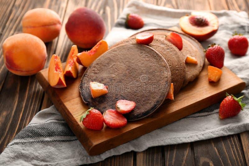 Вкусные блинчики шоколада с клубниками и отрезанным персиком на деревянной доске стоковое изображение rf