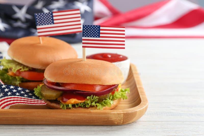 Вкусные бургеры с флагами США, который служат на таблице, космосе для текста стоковая фотография