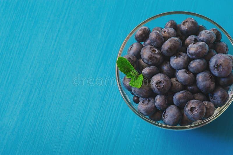 Вкусные голубики с мятой на голубой предпосылке Голубики противоокислительн органическое superfood стоковая фотография
