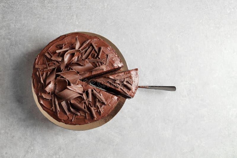 Вкусные домодельные шоколадный торт и лопаткоулавливатель с частью на таблице, взглядом сверху стоковое изображение rf