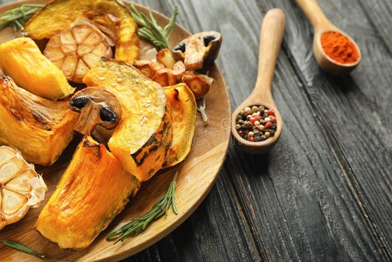 Вкусные испеченные части тыквы с грибами и чесноком на деревянной плите стоковое изображение