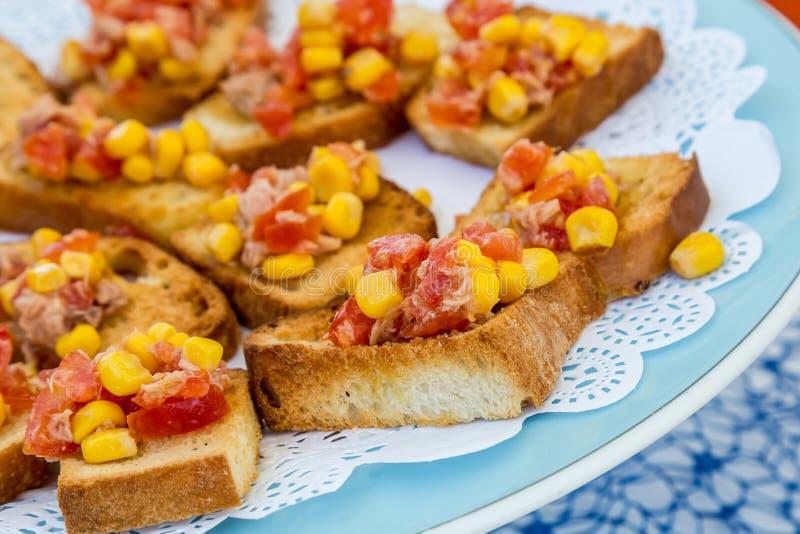Вкусные итальянские закуски помидора, брускетта, жареный хлеб, украшенный чесноком, кукурузой, базиликом, оливковым маслом стоковые фото