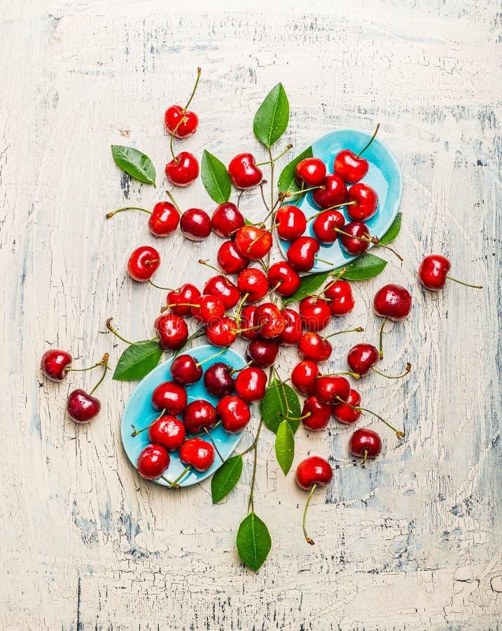 Вкусные красные вишни с листьями в голубых шарах и таблице, составлять взгляд сверху Плодоовощ и ягоды лета стоковые изображения