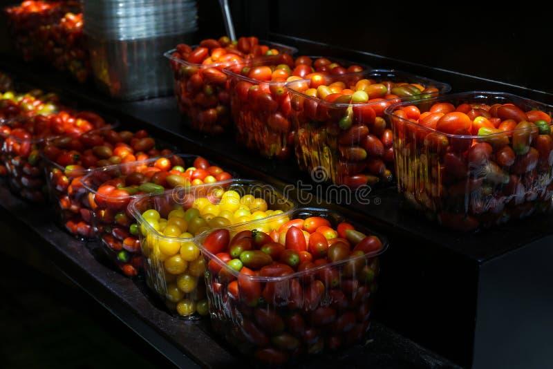 Вкусные красные и желтые томаты вишни на черной предпосылке стоковое изображение