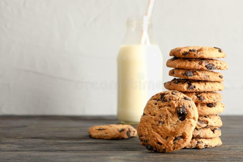 Вкусные печенья обломока шоколада и бутылка молока на деревянном столе стоковое изображение