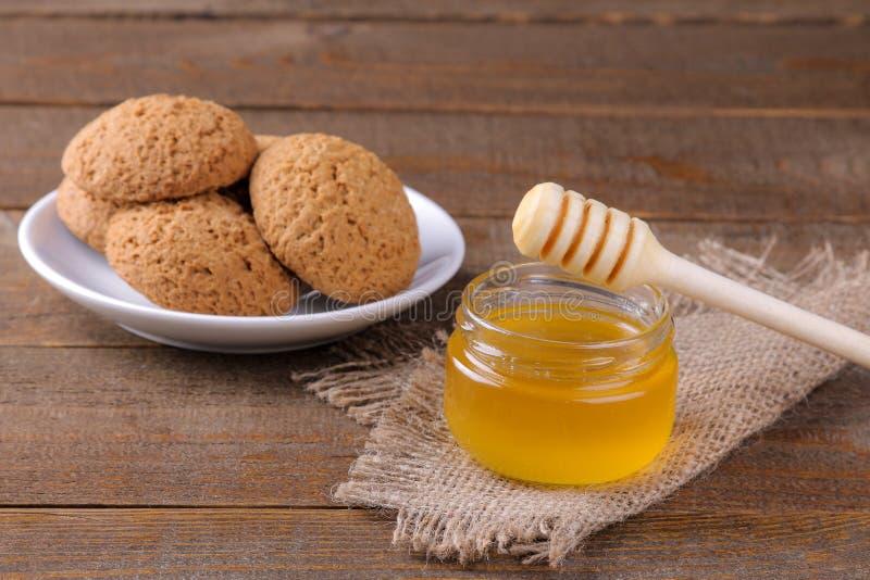 Вкусные печенья овсяной каши с медом на салфетке на коричневом деревянном столе стоковое изображение
