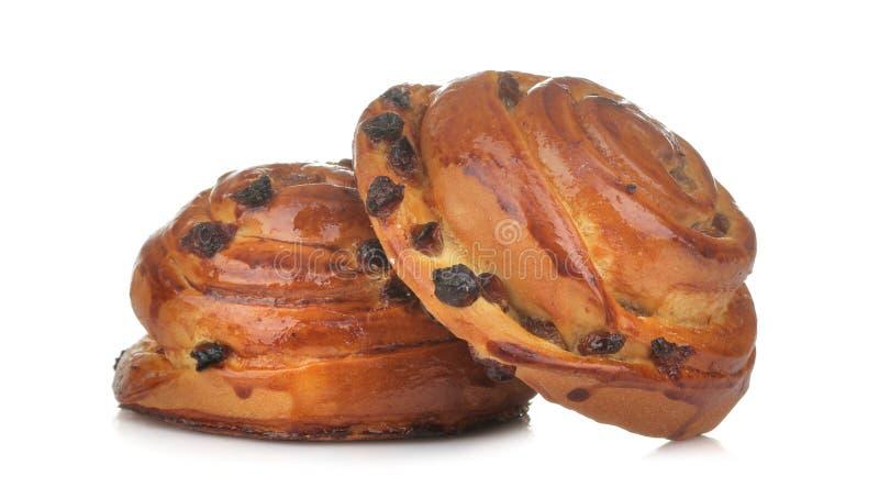 Вкусные плюшки с изюминками на белой изолированной предпосылке хлебопекарня свежая Конец-вверх стоковая фотография rf