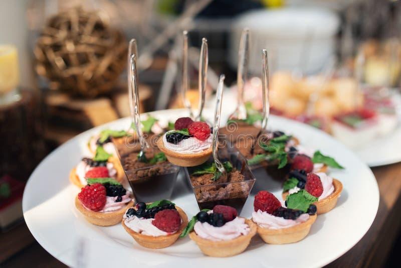 Вкусные помадки на коричневой деревенской деревянной таблице банкета Свадьба лета в таблице банкета леса Шоколадный батончик свад стоковая фотография