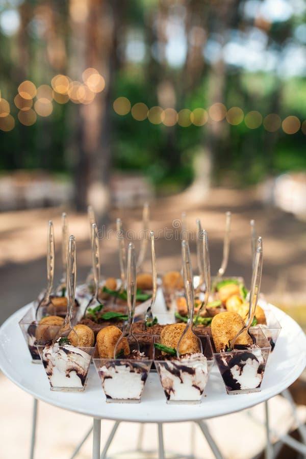 Вкусные помадки на коричневой деревенской деревянной таблице банкета Свадьба лета в таблице банкета леса стоковые фото
