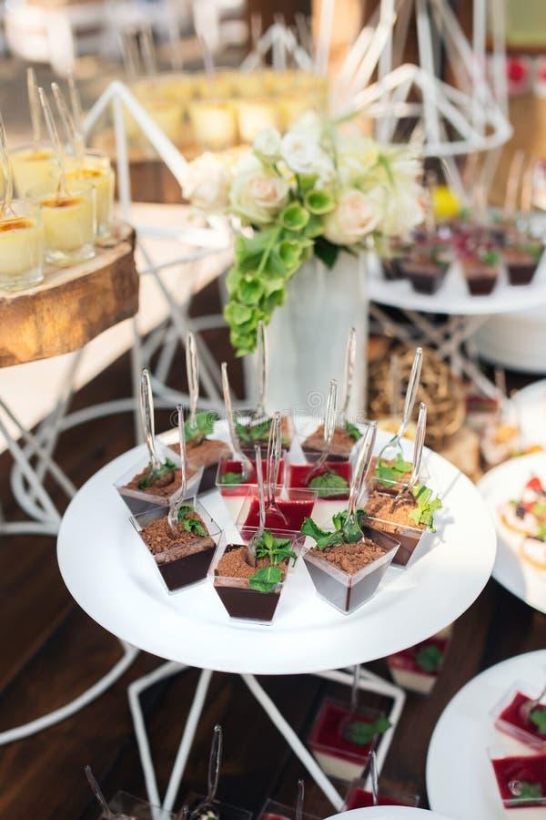 Вкусные помадки на коричневой деревенской деревянной таблице банкета Свадьба лета в таблице банкета леса стоковые фотографии rf
