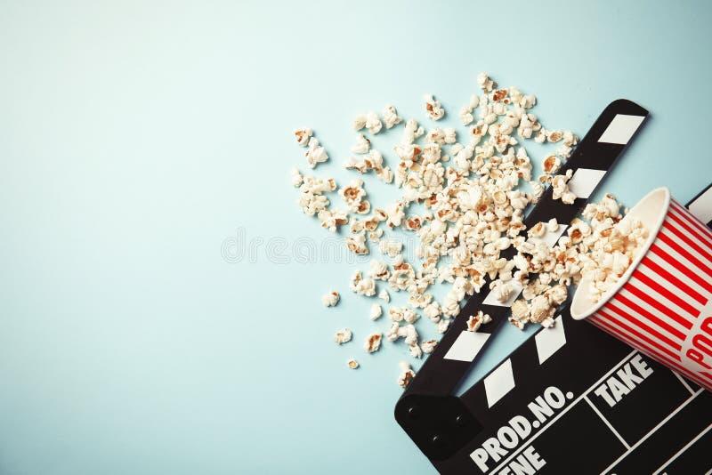 Вкусные попкорн и clapperboard на предпосылке цвета, взгляд сверху с космосом для текста стоковые фото