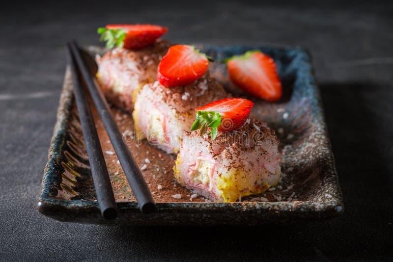 Вкусные сладкие суши с циннамоном и шоколадом на конкретной таблице стоковые изображения