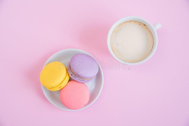 Вкусные сладкие macarons на плите и чашке душистого кофе утра Французские macaroons на розовой предпосылке стоковая фотография rf