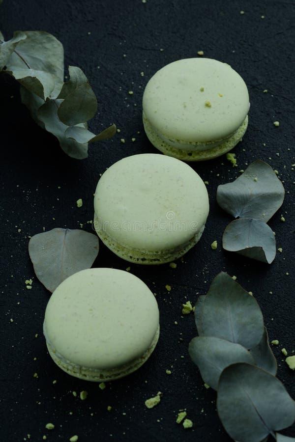 Вкусные сладостные зеленые macarons испекут на темной предпосылке, темном настроении стоковые фотографии rf