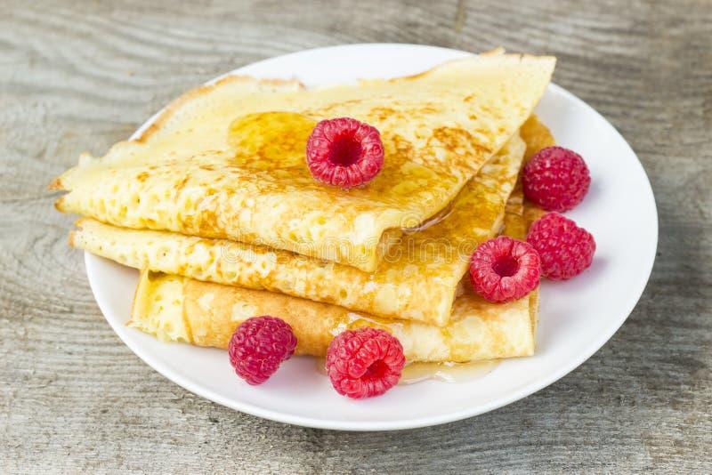 Вкусные сладостные тонкие блинчики с свежими полениками и медом на плите, очень вкусном десерте, крупном плане, деревянной предпо стоковое изображение