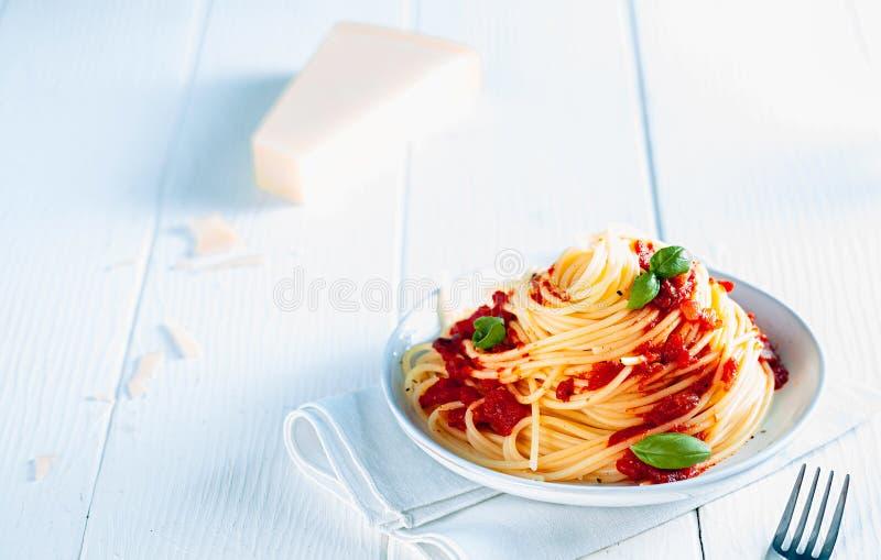 Вкусные спагетти в плите на белой предпосылке таблицы стоковые изображения rf