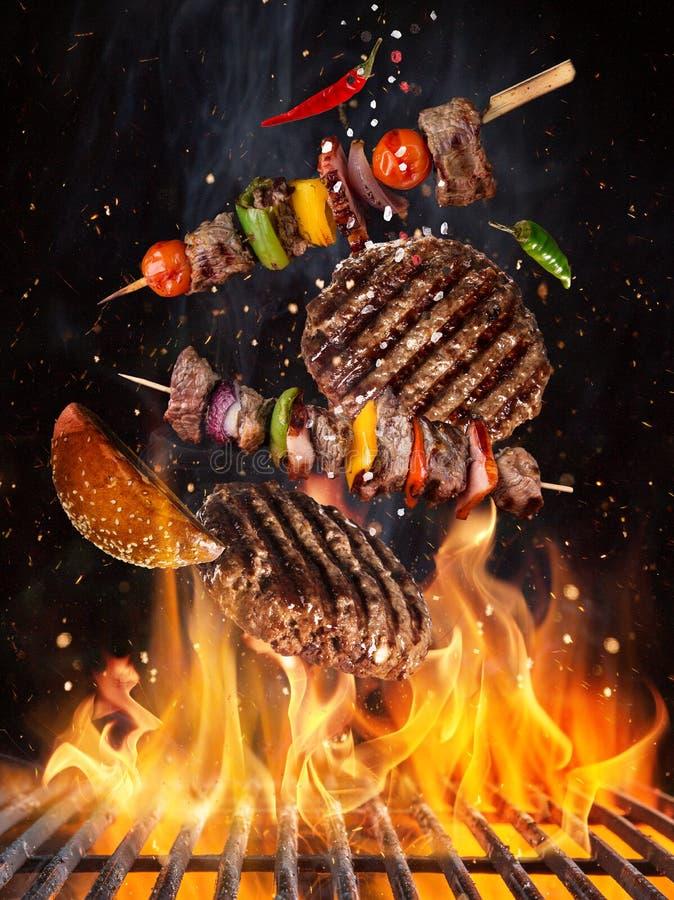Вкусные стейки говядины и протыкальники летая над решеткой литого железа с пламенами огня стоковые фото