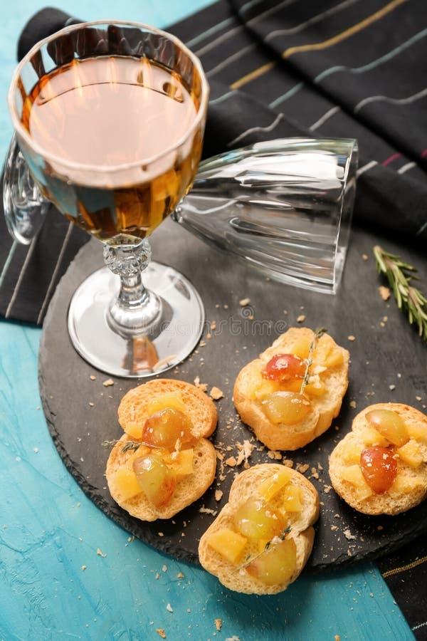 Вкусные сэндвичи с виноградиной, сыром и бокалом вина на плите шифера стоковые фотографии rf