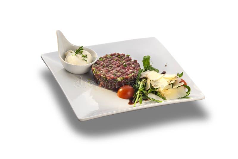 Вкусные тартар стейка и салат ракеты с сыром готовым для служения стоковые фото