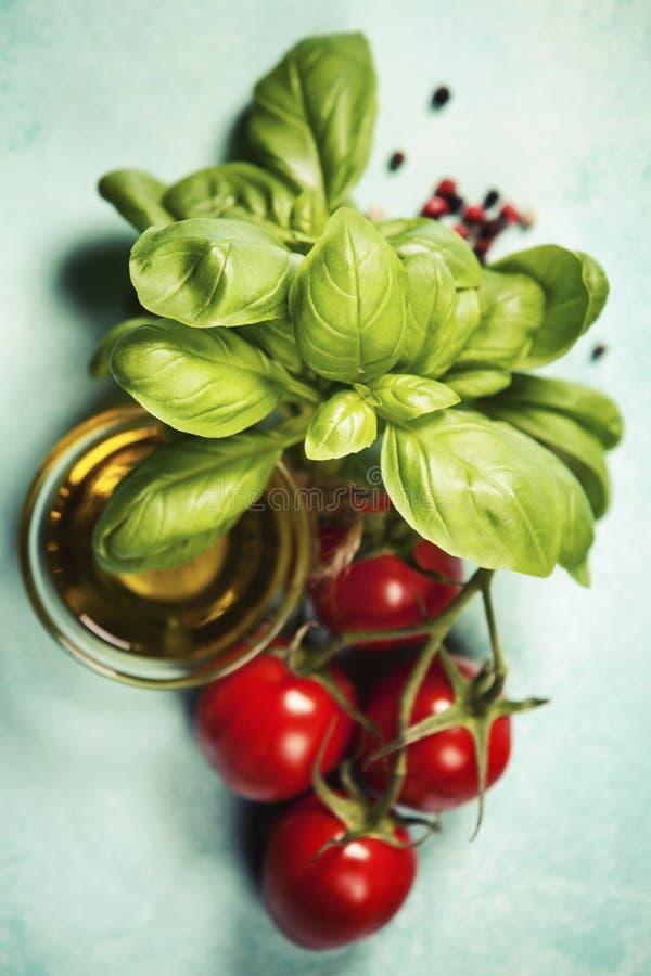 Вкусные томаты с свежими листьями базилика и оливковым маслом стоковая фотография rf